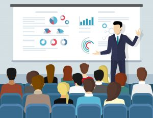 Image of an executive giving a powerpoint presentation in front of an audience